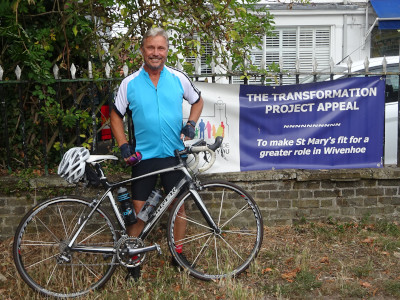 Terry standing by his bike in front of Transformation Project banner